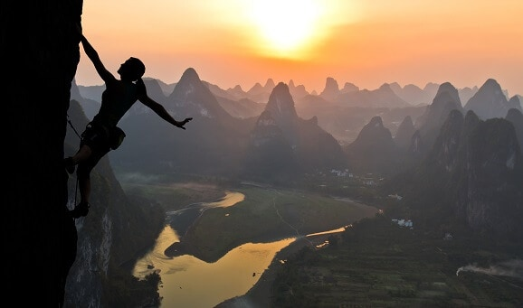 woman achieving her goal by climbing mountain at sunrise