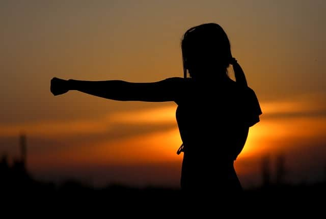 strong woman throwing punch at sunset
