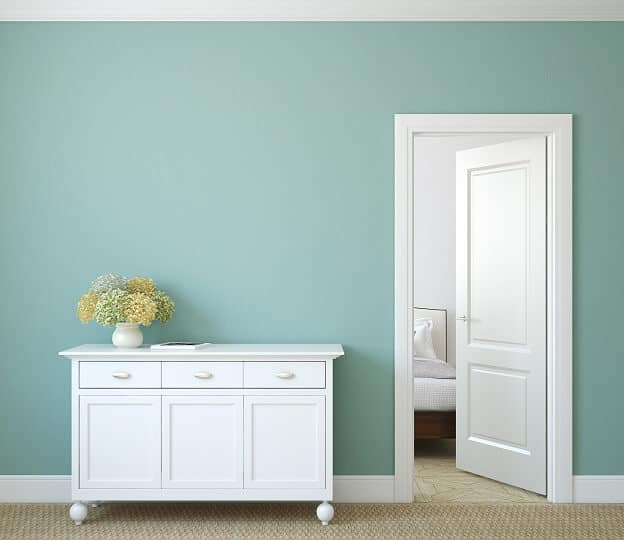white sideboard with flowers in vase against aqua wall with white trim and door partially open to bedroom