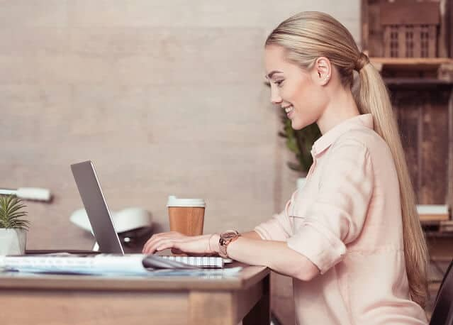 young woman working diligently on laptop