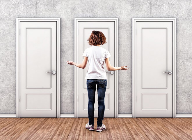 woman standing in front of three doors stressed with too many choices