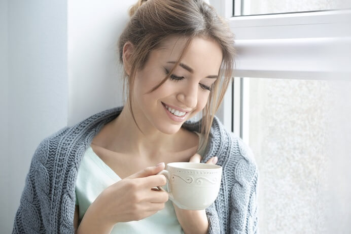 happy woman wearing gray sweater drinking coffee no decision fatigue