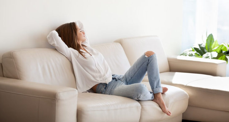 woman relaxing on white couch in a clutter-free home