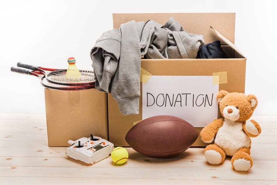 boxes of toys and sports equipment ready to donate after decluttering