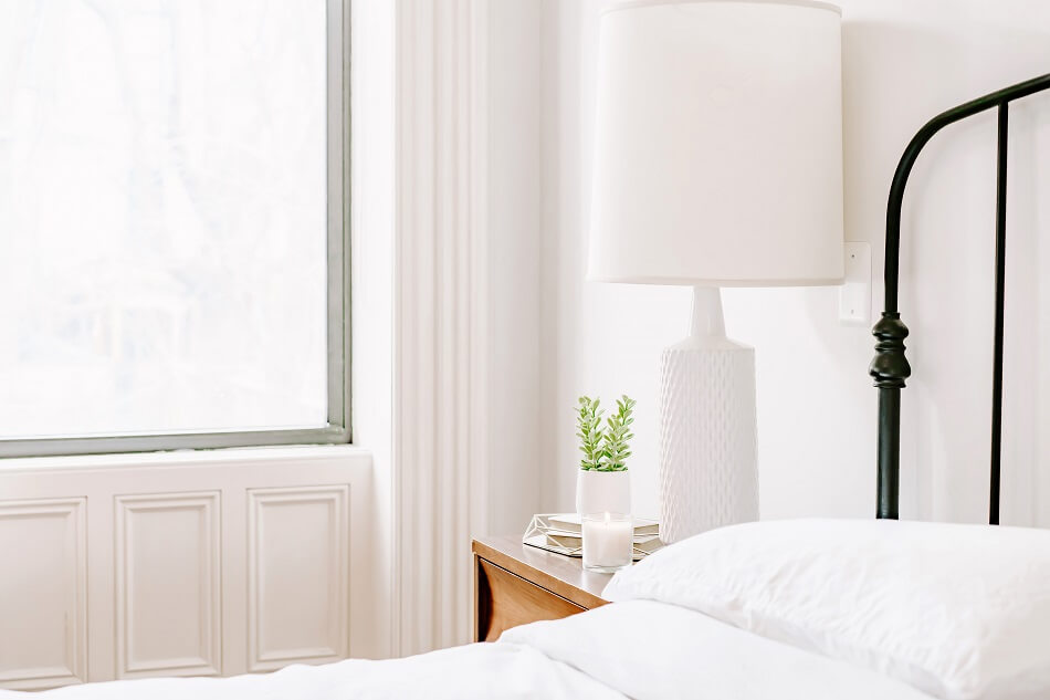 clutter-free white bedroom with bed and lamp near window