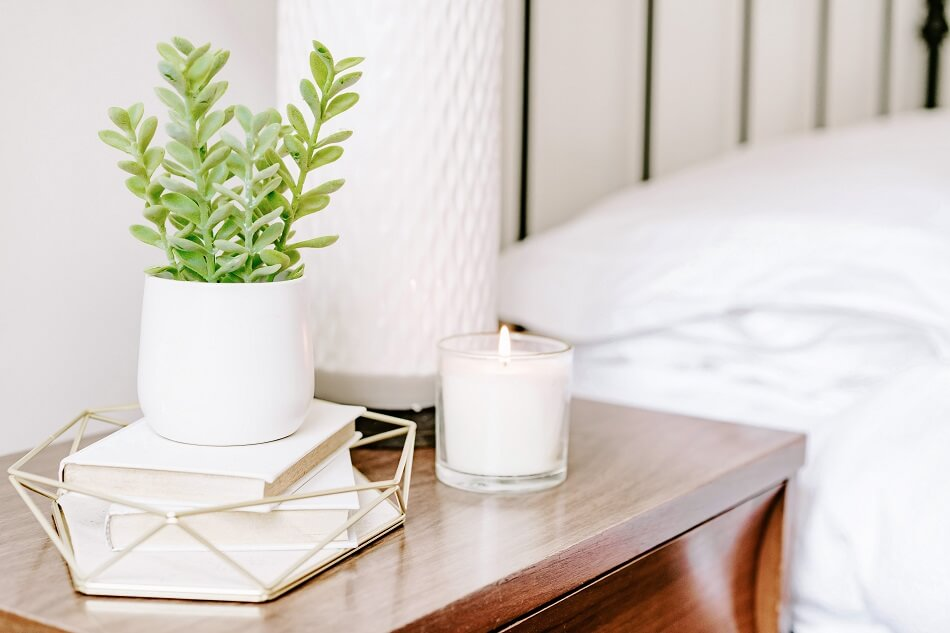 white clutter-free bedroom with table, books, plant, candle, lamp