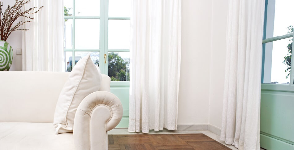 white couch in clutter-free living room with windows and white curtains