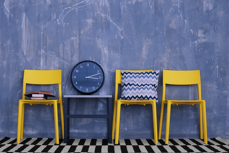 yellow chairs blue chevron pillow books and clock against blue wall