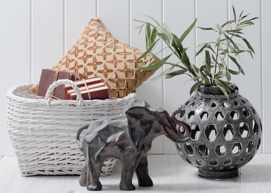 decorations to be decluttered - elephant statue, planter, basket with pillow and books against white wall