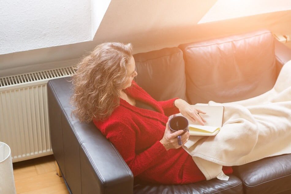 brunette woman wearing red sweater holding mug sitting on leather couch with blanket and journal while feeling lazy