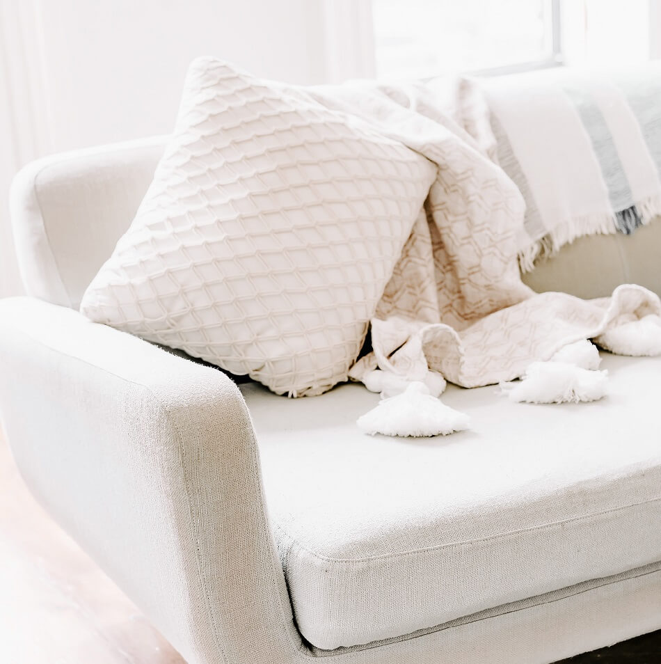 bright room with white couch pillow and blanket ready for a lazy day