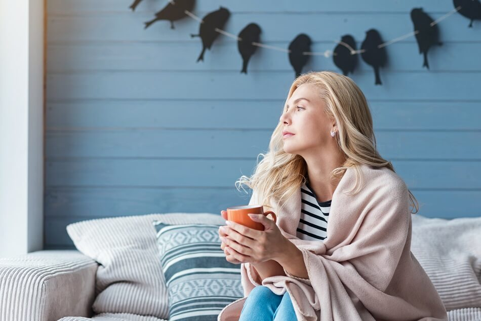 blonde woman holding orange mug sitting on couch looking into distance while considering what to do when feeling lazy