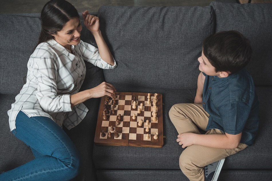 mother and son sitting on dark gray couch and playing chess to build positive relationship