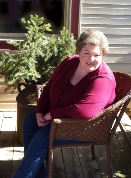 woman with short blond hair wearing jeans and red sweater sitting in wicker chair on porch against greenery and tan siding background