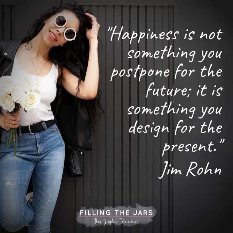 woman in jeans and white shirt holding white flowers against black background with text overlay quote jim rohn happiness