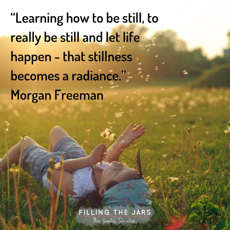 child lying in grass during summer blowing dandelion seeds with text overlay quote morgan freeman stillness becomes radiance