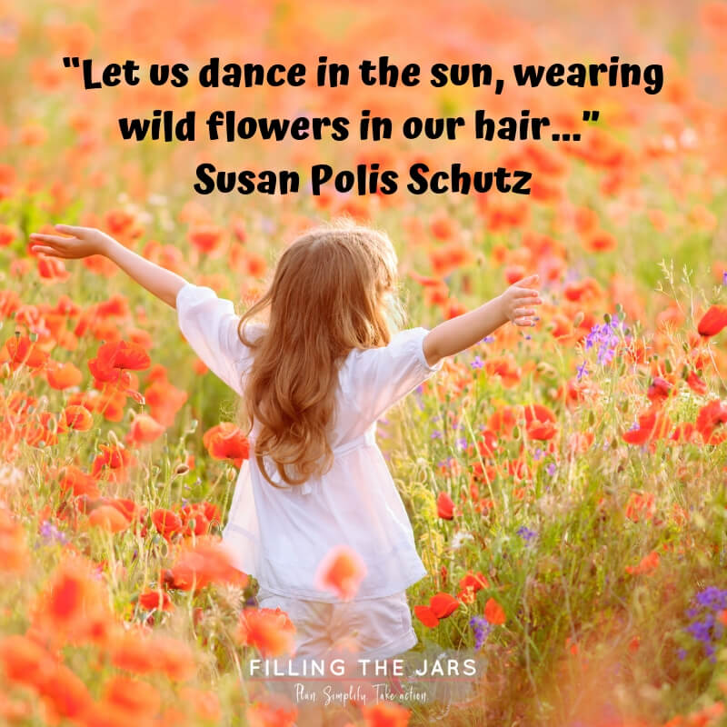 little girl standing in field of wildflowers with text overlay quote susan polis schutz dance in the sun