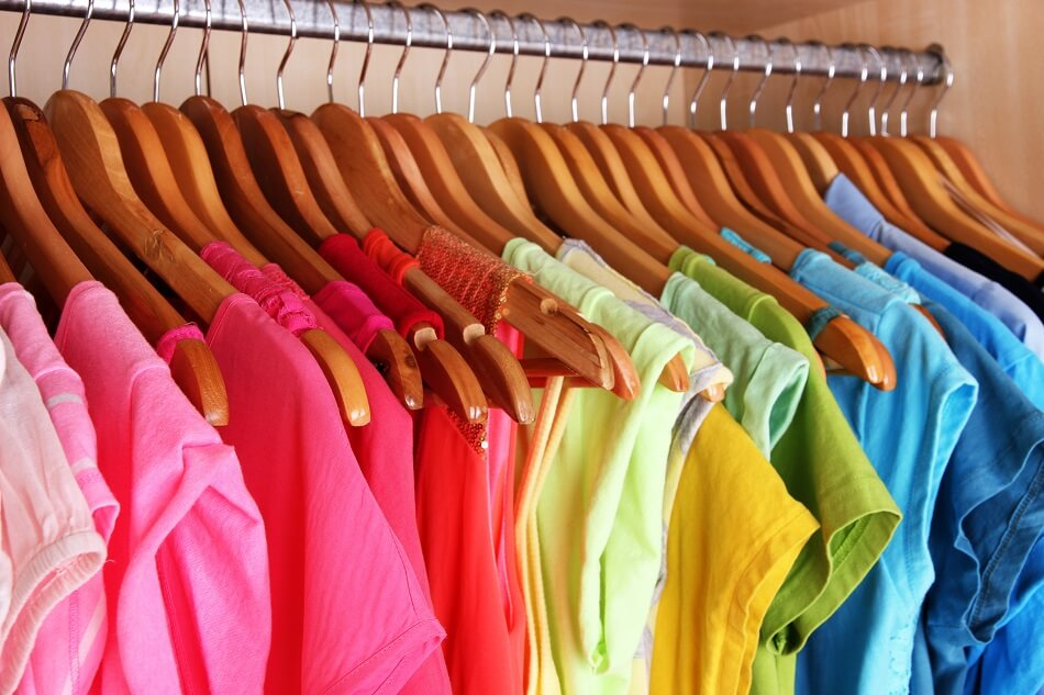 bright rainbow of shirts hanging in clutter-free closet