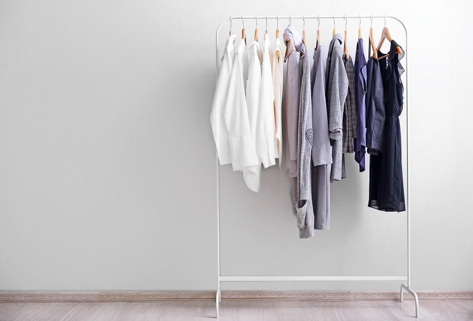 simple decluttered wardrobe in neutral tones hanging on white clothing rack against white wall