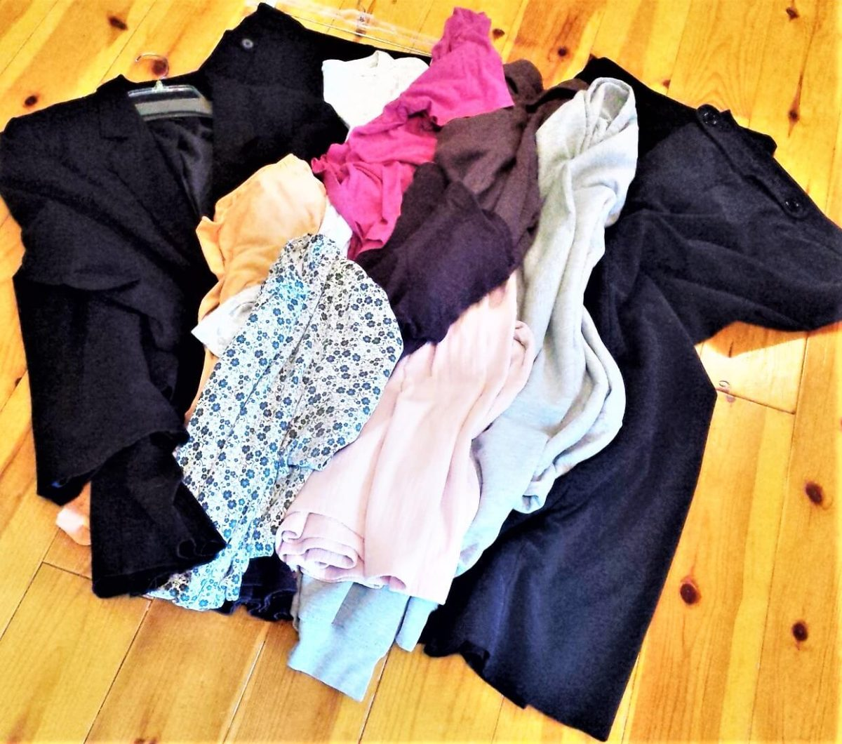 pile of decluttered clothing on wood floor