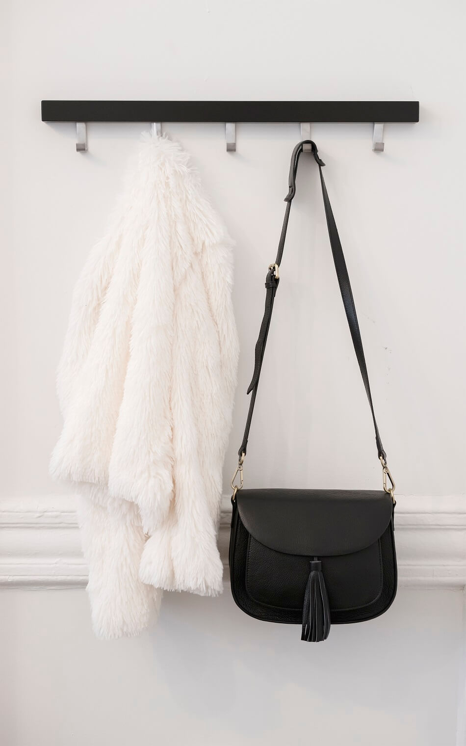 white jacket and black purse hanging against white wall