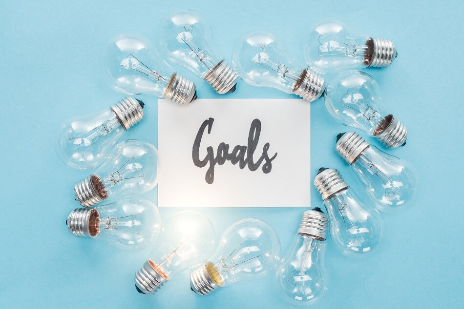 lightbulbs and goals paper on blue background