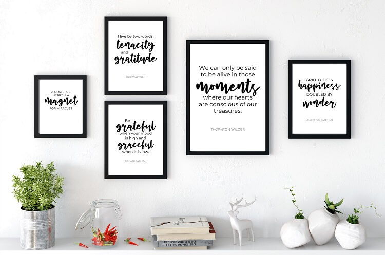 free printable black and white gratitude quotes in black frames on white wall above shelf with home decor items