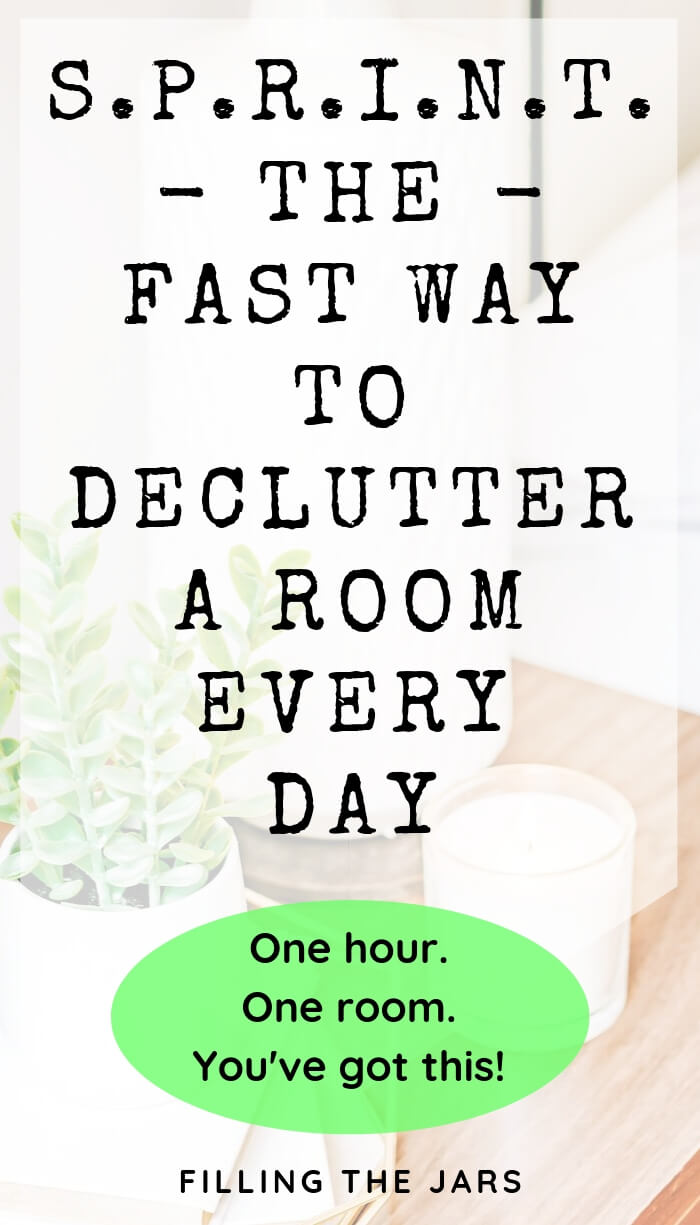 plant and candle on wood table with white overlay and text the fast way to declutter a room