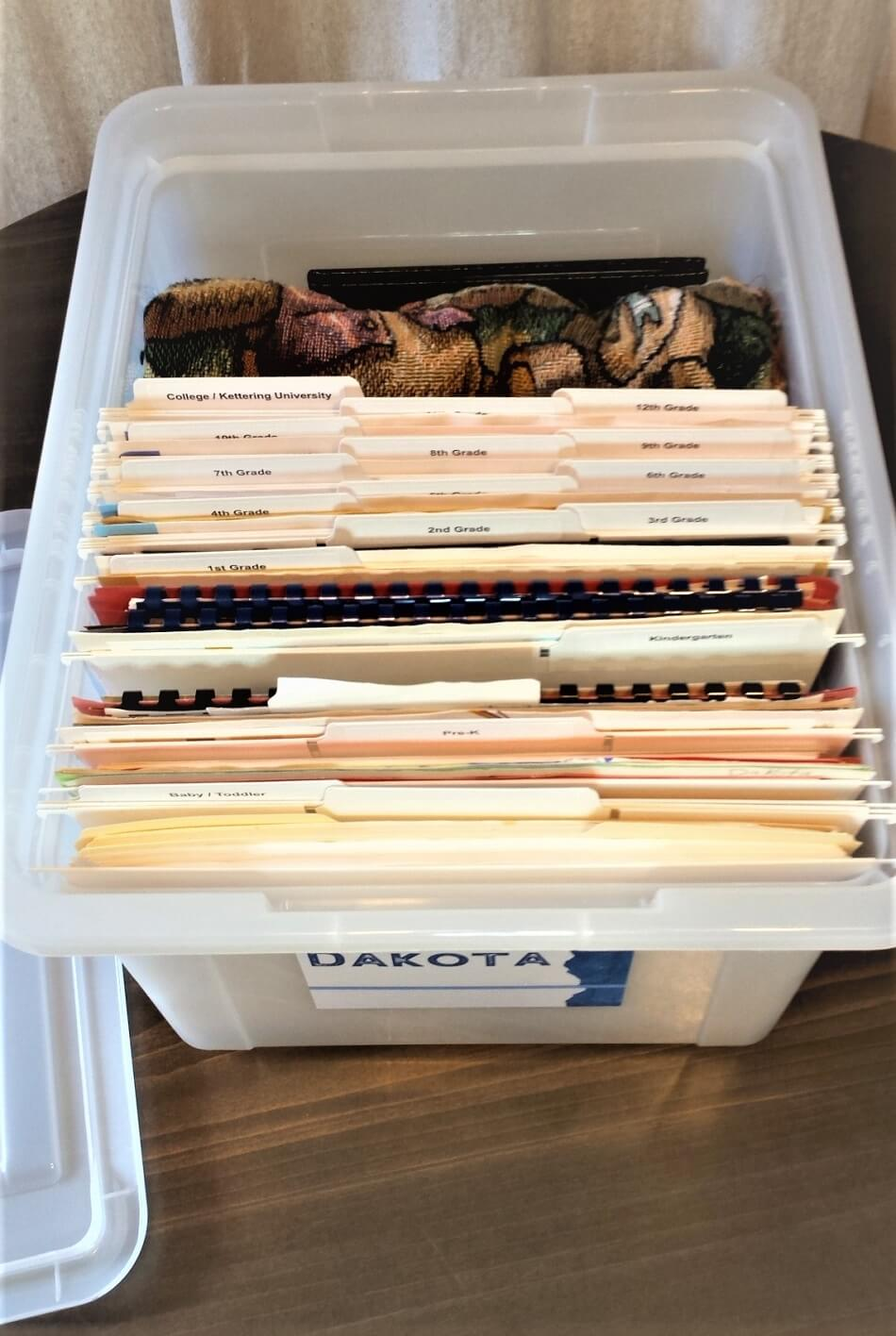 white memory box with organized school papers in white files