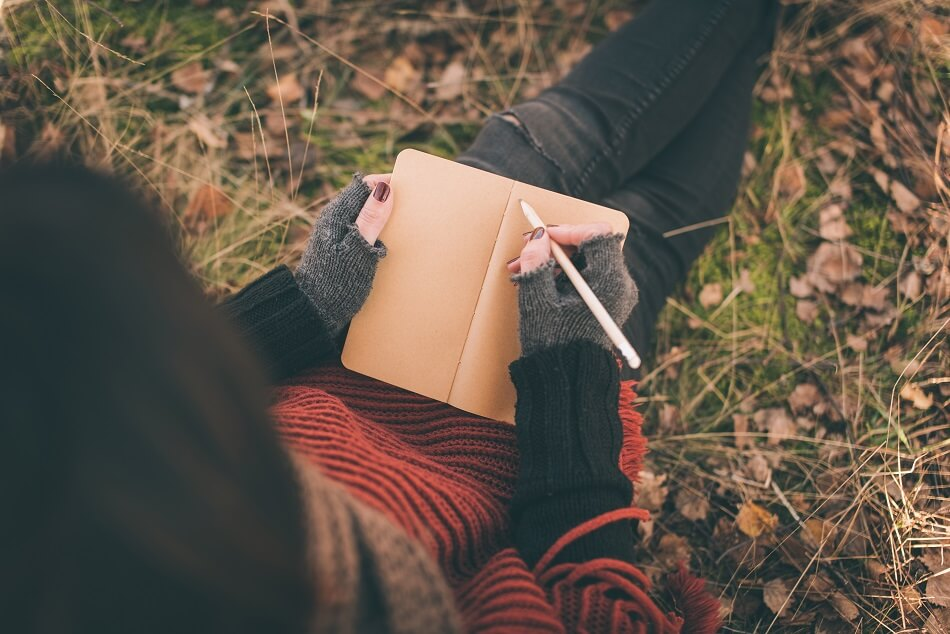 woman in red and black sweater and black jeans sitting on autumn grass and leaves while writing in journal