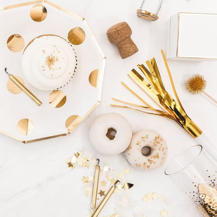 gold and white party food and decor on white background