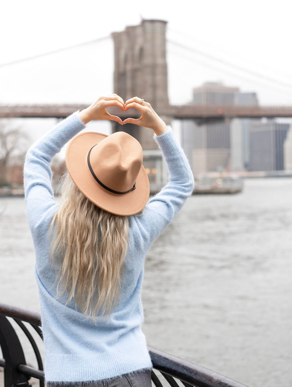 blonde woman in blue sweater and hat making heart sign with hand against background of brooklyn bridge