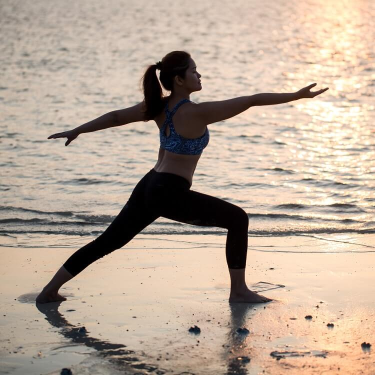 woman conquering laziness and exercising on beach at sunrise