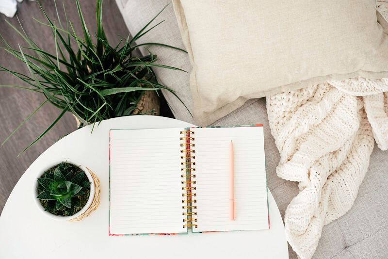cozy couch with pillow and blanket next to plants and white table with open journal ready to use for february daily writing prompts