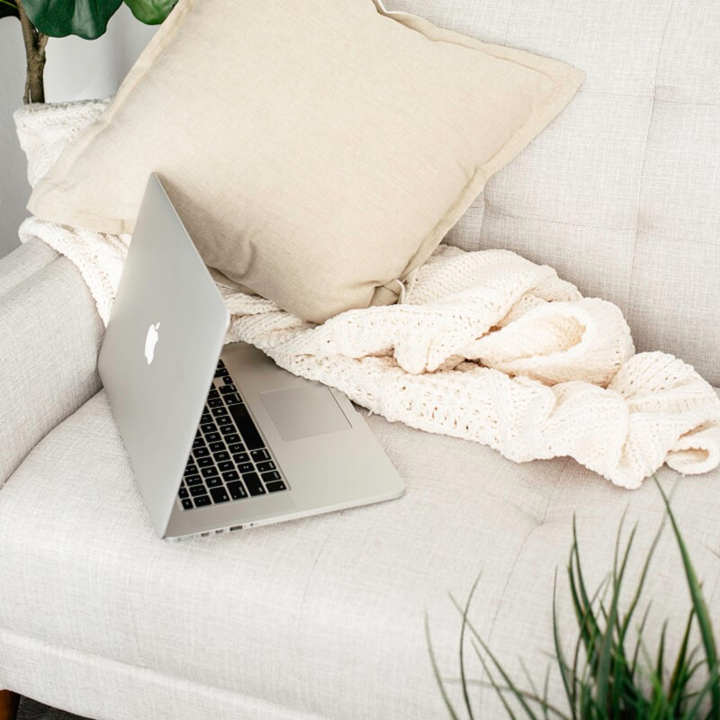 laptop and blanket left on white couch after owner got up and decided to stop being lazy