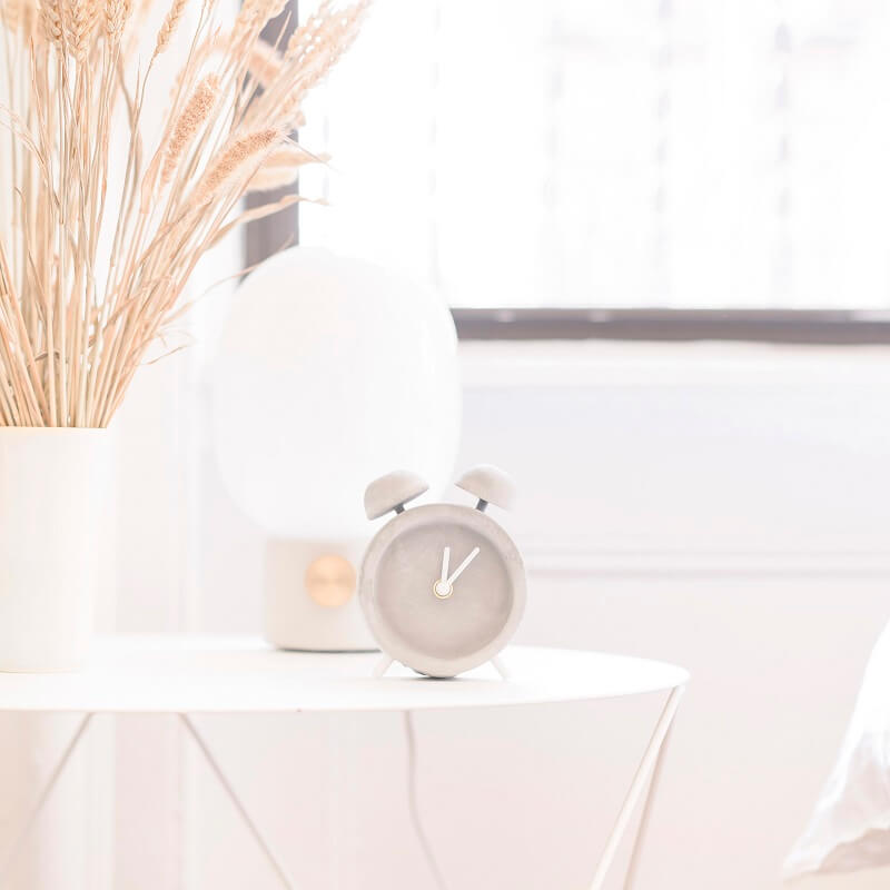 clock lamp and vase of wheat on white table with morning light streaming through bedroom window