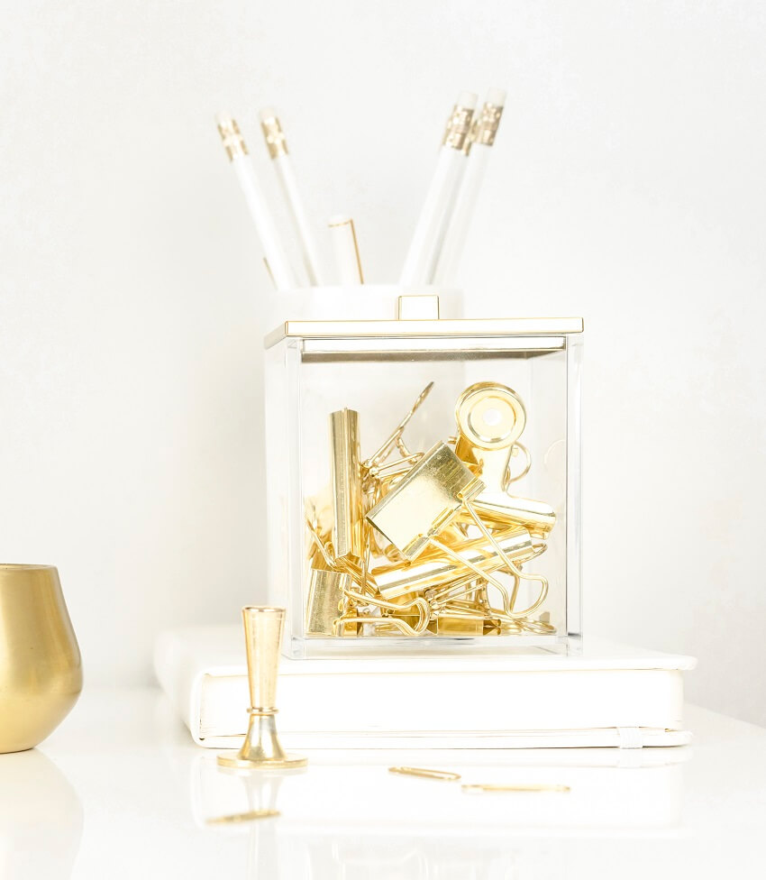 jumbled gold binder clips and office supplies on white desk against white wall