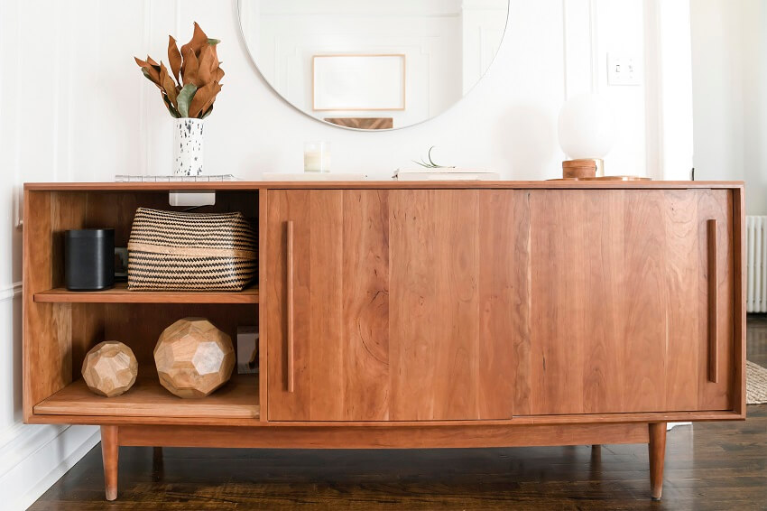 wood credenza against white wall with neutral color decor