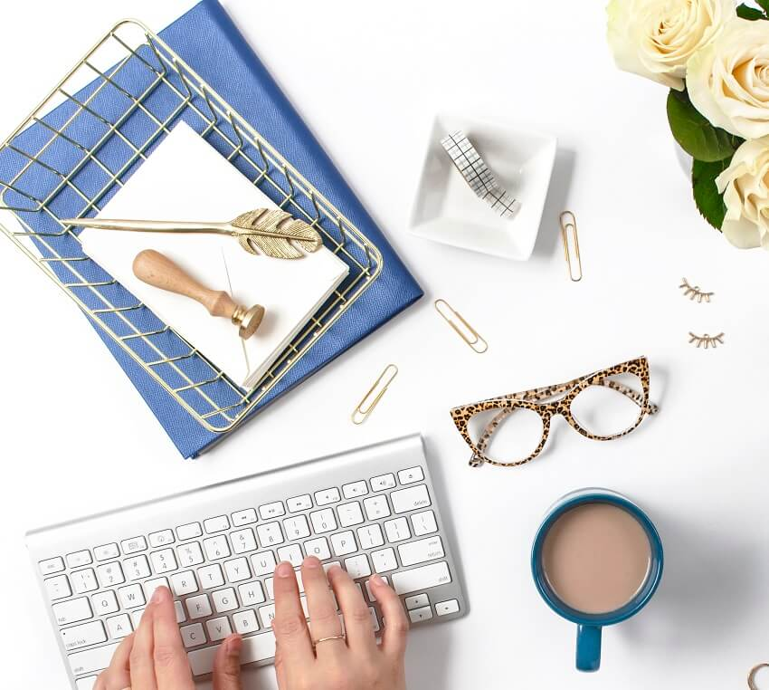 hands typing on keyboard surrounded by glasses, coffee and office items on white desk
