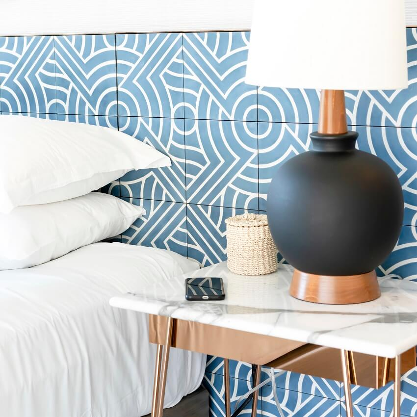 clutter-free bedroom with blue and white tile wall and lamp with black base on tidy bedside table