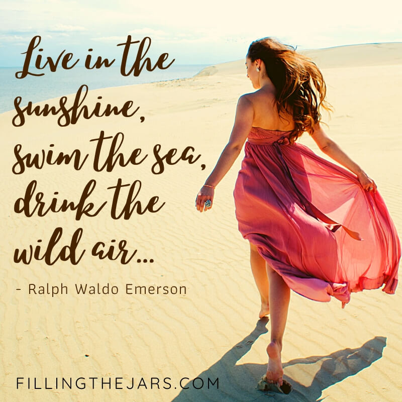 background of sand and ocean with woman in pink dress walking away and overlay Ralph Waldo Emerson live in the sunshine quote