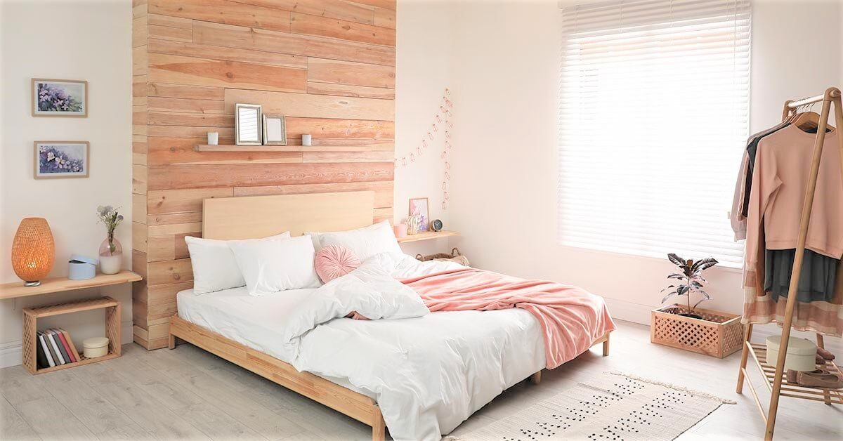 minimalist bedroom with wood bed and wall and white bedding peach accents and freestanding clothes rack