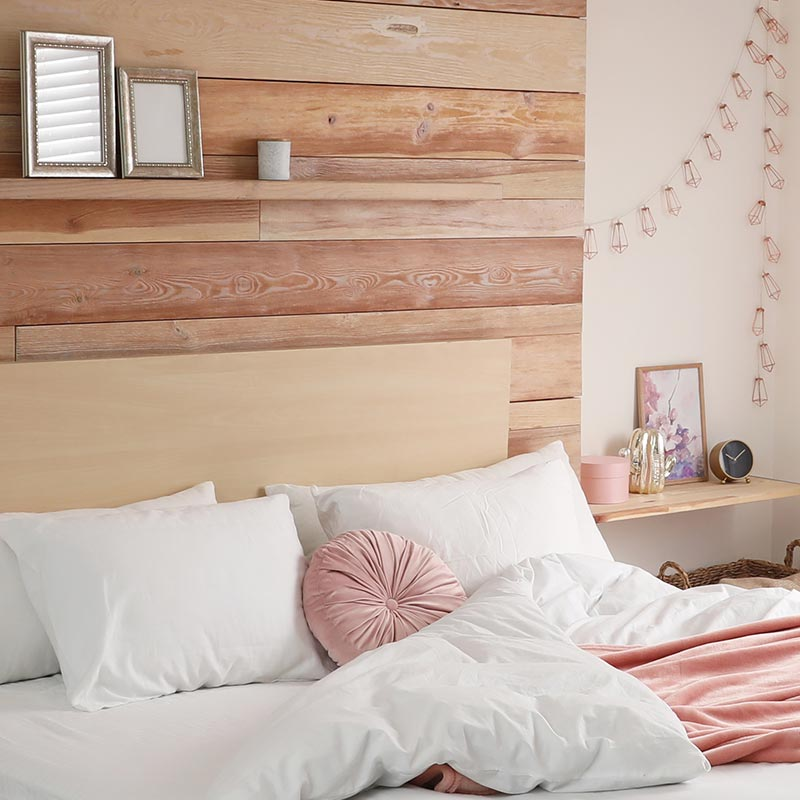 clutter-free minimalist bedroom wood and white walls white bedding peach accents wood shelf
