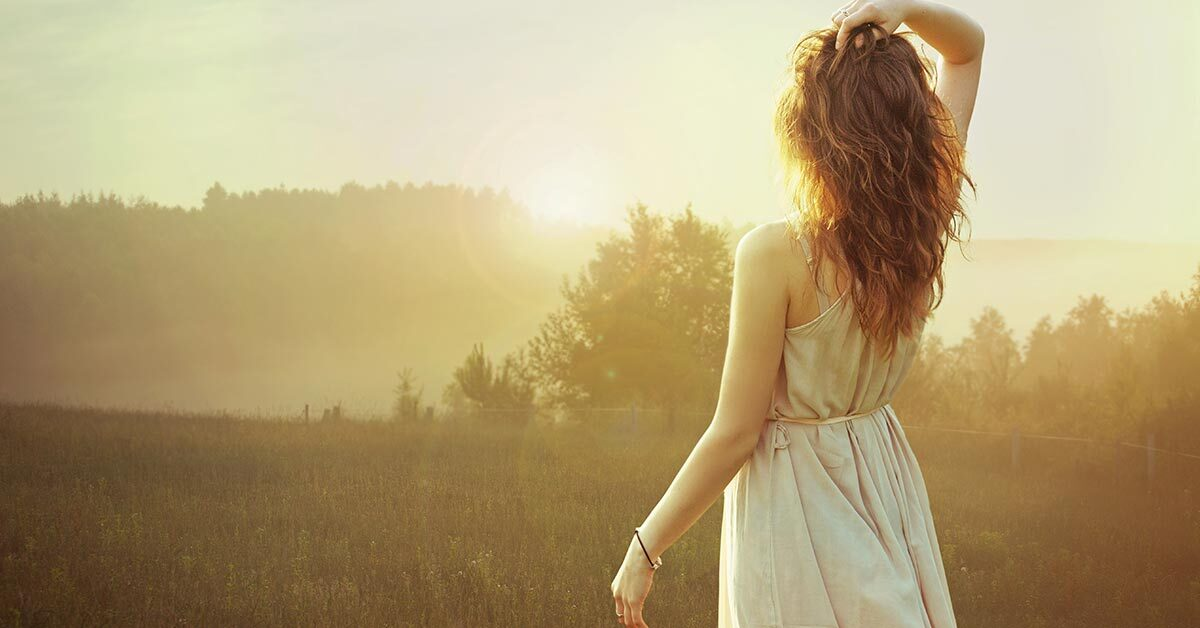woman with long dark hair and casual white dress watching inspirational summer morning sunrise