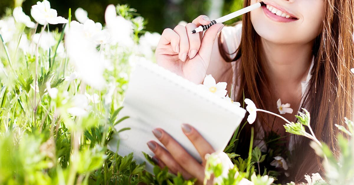 young woman lying in wildflower field on sunny day while getting ready to journal in notebook