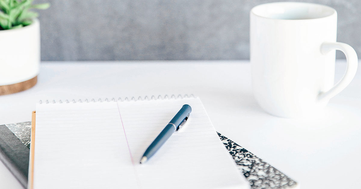 blue pen lying on notebooks next to white coffee mug on white desk