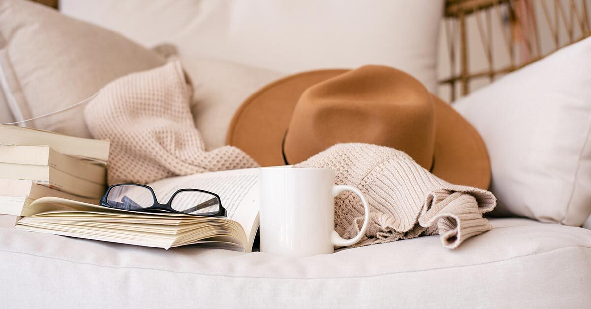 comfortable white couch with cowboy hat coffee mug glasses cozy blanket glasses and books