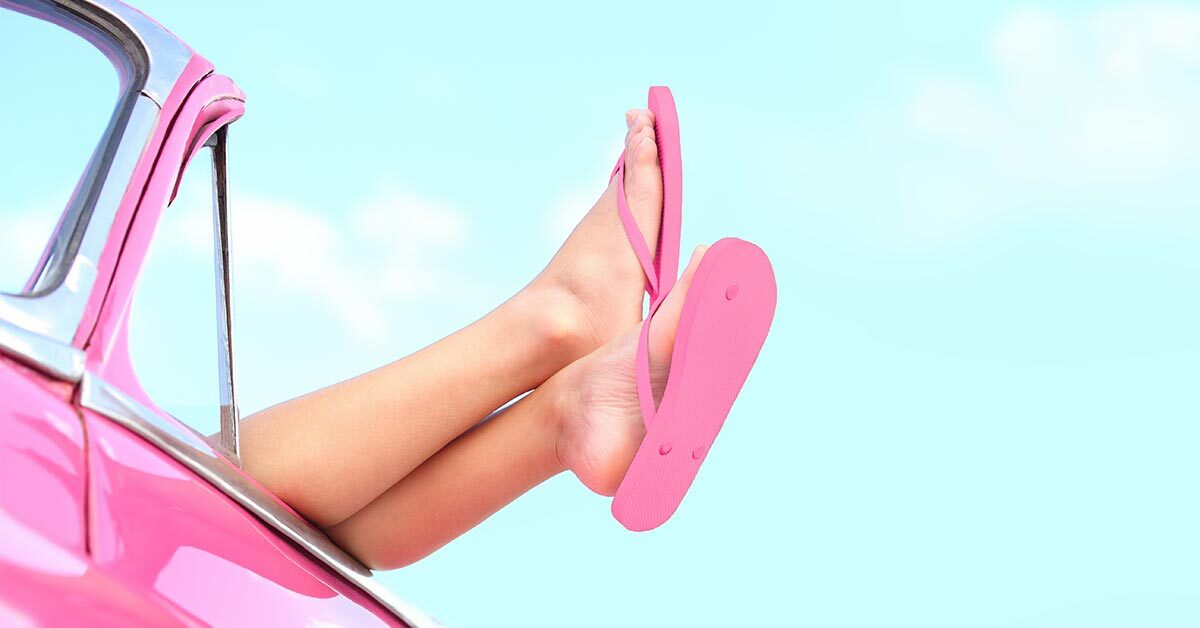 summer sky background with vintage pink car and female legs wearing pink flip flops hanging over door