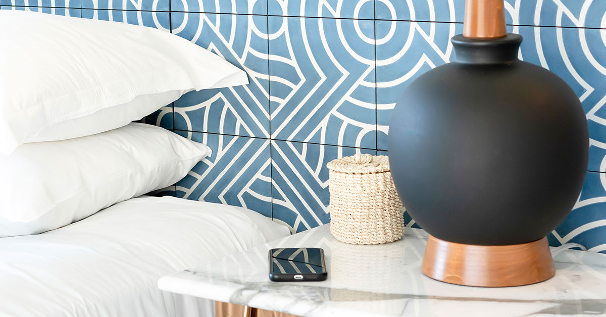 white pillows on bed and black lamp with phone on bedside table against blue patterned wall
