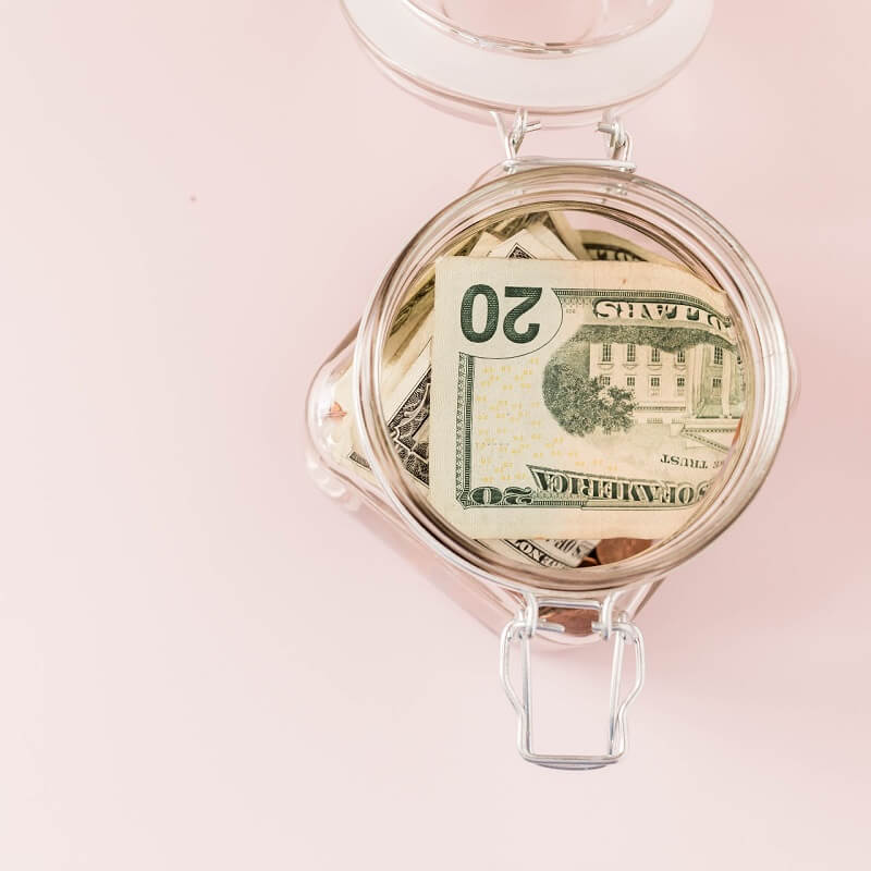 pink background with glass jar of money saved during no spend month